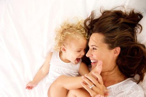 view portrait of happy mother and daughter lying on bed at home-img-blog