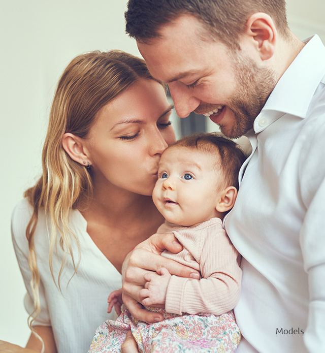 Mother kissing baby father is holding