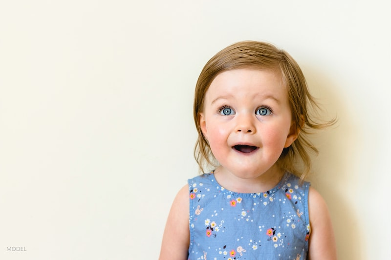 A toddler open-mouthed in delight.
