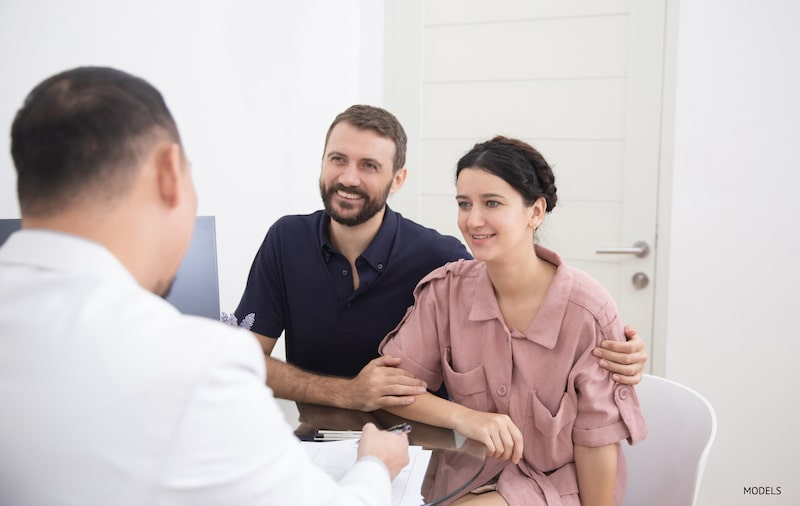 A couple consulting with a doctor in an office