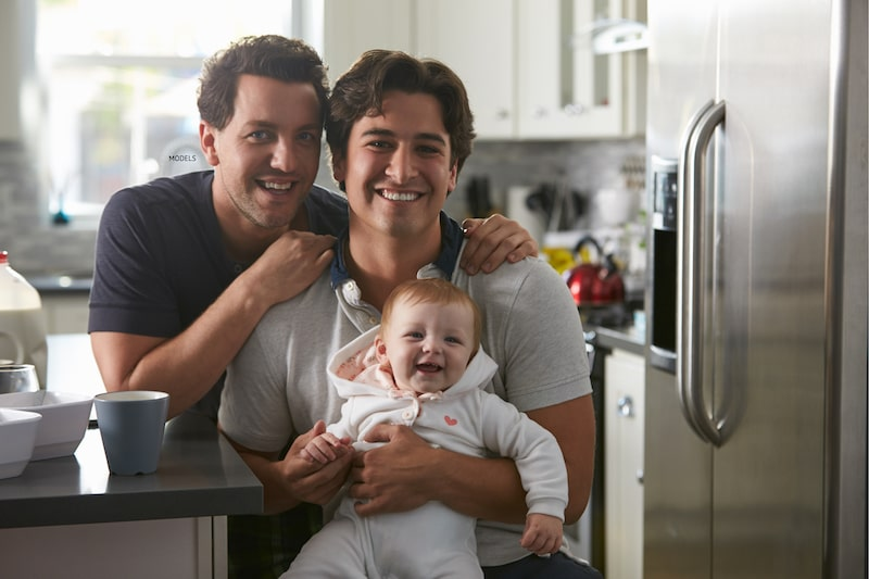 Two men sitting at a kitchen counter with a baby.